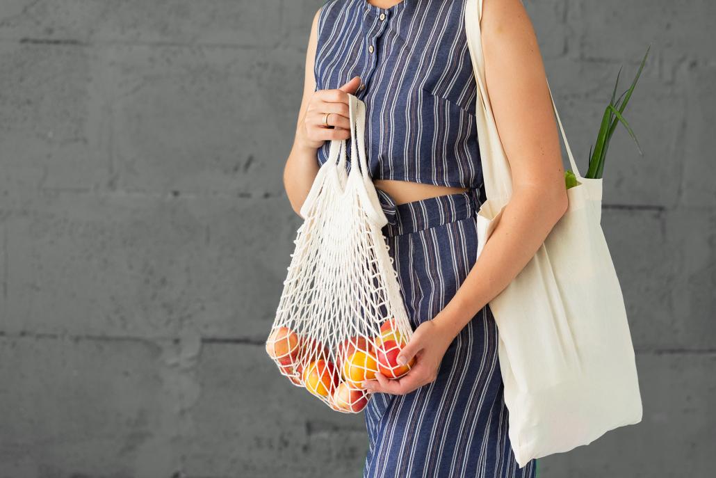 Zukunftsthemen: Nachhaltigkeit. Im Bildbeispiel kommt eine junge Frau mit nachhaltigen Einkaufstaschen vom Einkauf